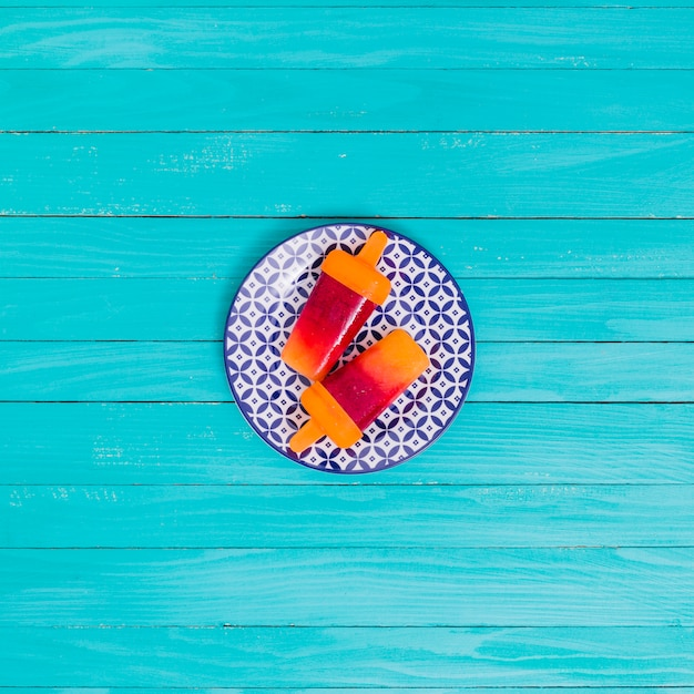 Bright fruit popsicle on plate on wooden surface Free Photo