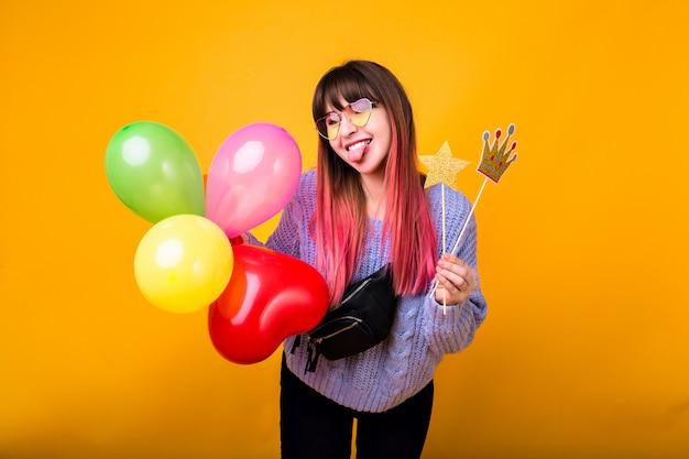 Яркий смешной портрет веселой хипстерской женщины с ярко-розовыми волосами, одетой в уютный свитер, держащей поддельную вечеринку и улыбающейся, готовой к вечеринке, желтой стене. Бесплатные Фотографии