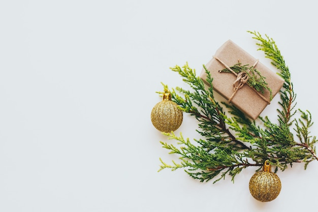 Bright green twigs of pine tree and a light brown gift box and golden balls Premium Photo