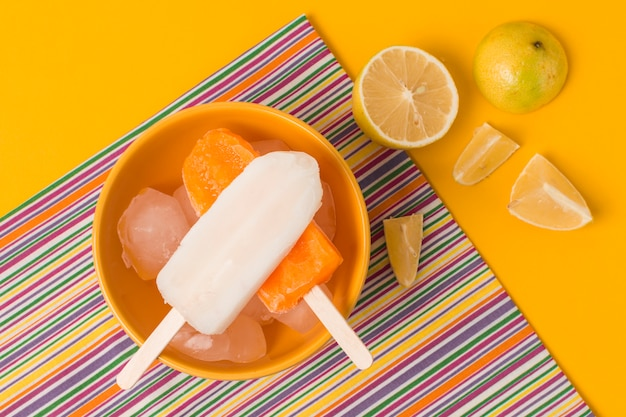 Bright ice lolly in bowl near napkin and fresh fruits Free Photo