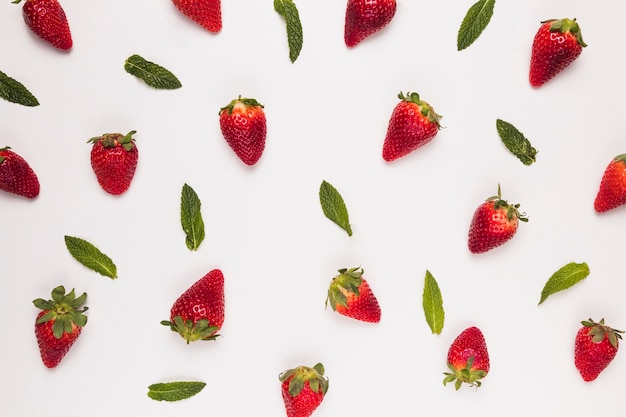 Bright juicy strawberries and green leaves on  white background Free Photo