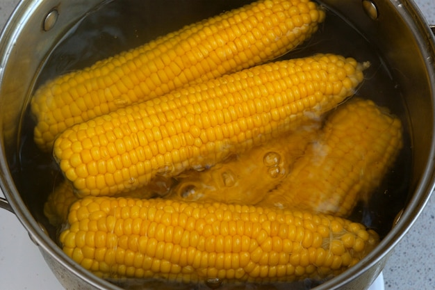 Bright juicy yellow corn, which is boiled in boiling water on the stove close-up. delicious young sweet sugar corn. summer healthy vegetables with vitamins. Premium Photo