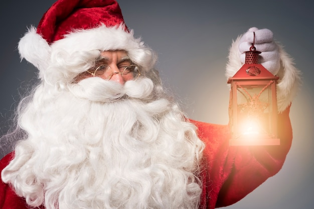 산타 클로스가 들고있는 밝은 등불 무료 사진