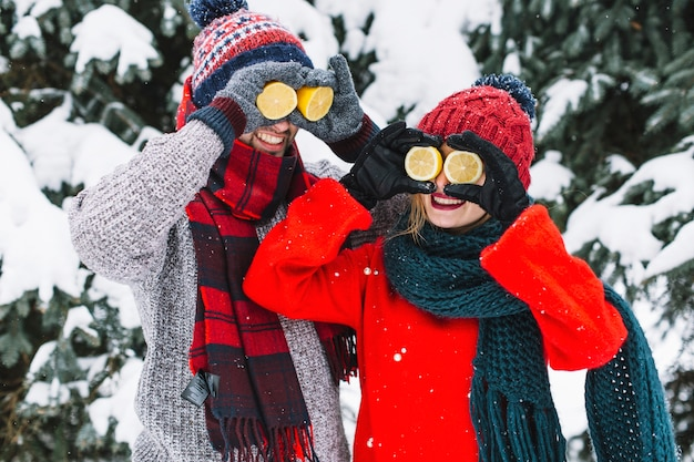 Bright laughing couple with lemons in winter Free Photo