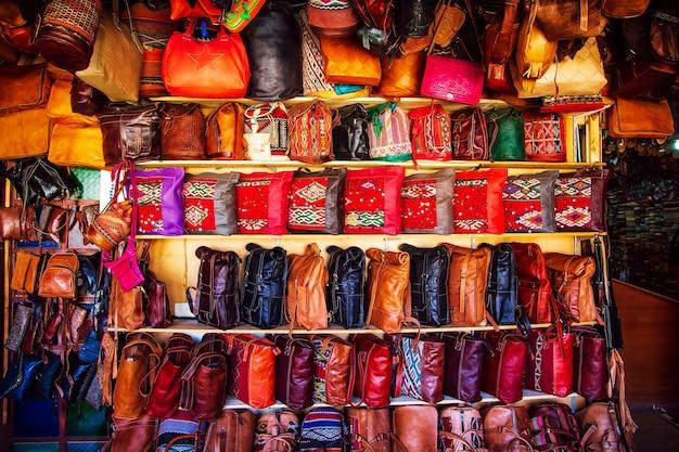 Яркие кожаные сумки на марокканском рынке. сувениры ручной работы, фес, марокко. Premium Фотографии