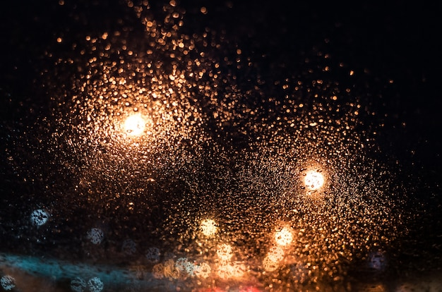 The bright lights of the night city through the glass in the drops of rain. Premium Photo