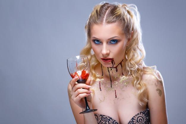 Яркий макияж на лице красивой женщины с бокалом вина в руке Premium Фотографии