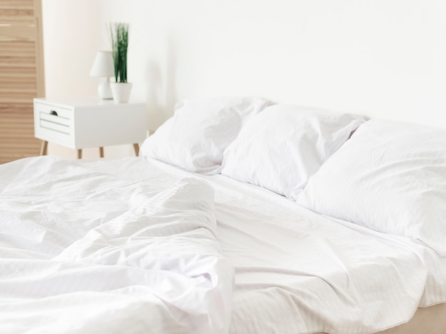 Bright modern bedroom with white sheets Free Photo