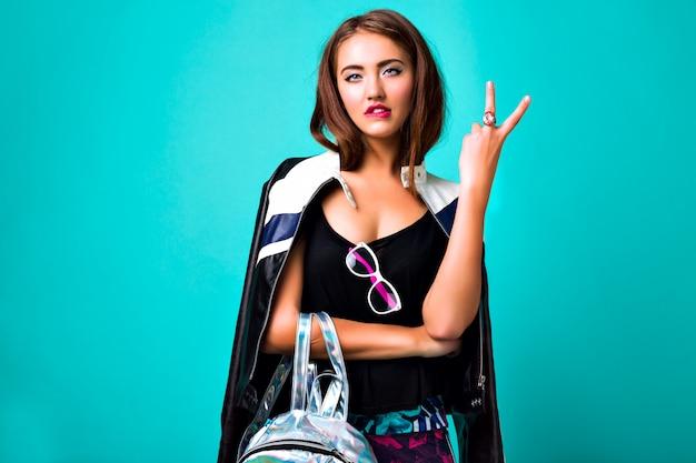 生意気な美しいトレンディな女性、明るい服、アクセサリーの明るいネオンファッションポートレート、ヒップスタースタイル、革のジャケット、バックパック、若いモデル 無料写真