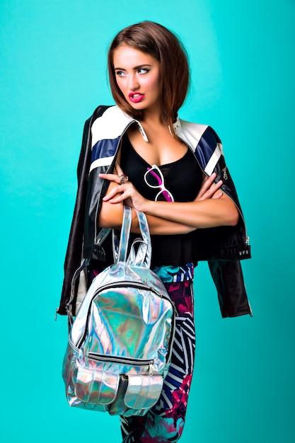 生意気なトレンディな女性、革のジャケット、バックパック、若いモデルの明るいネオンファッションポートレート 無料写真