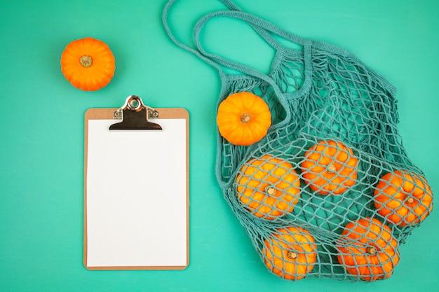 Ярко-оранжевые тыквы в сетчатой сумке и пустом блокноте для списка покупок или рецепта Premium Фотографии