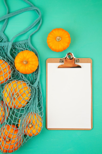 Bright orange pumpkins in mesh bag and empty notepad for shopping list or recipe Premium Photo