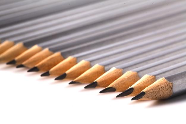 白いテーブルにたっぷりの同じ黒い仲間の群衆から目立つ明るい鉛筆。リーダーシップ、ビジネスの成功の概念 Premium写真
