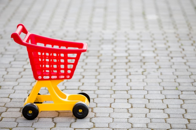 Bright plastic colorful shopping cart toy outdoors on sunny summer day Premium Photo