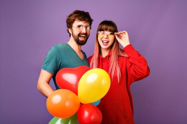 楽しんで、舌を見せて、パーティーの気球を持っているカップルのヒップスター、一緒に親友、カジュアルなスポーティーな服の明るくポジティブなライフスタイルの肖像画 無料写真