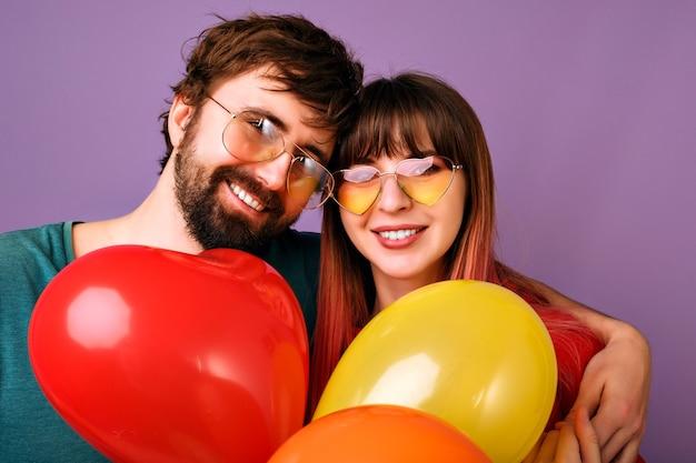 幸せなかわいいカップルの笑顔、平和のジェスチャーを示し、パーティーの風船、家族関係、紫の壁を保持しているの明るい肯定的な肖像画 無料写真