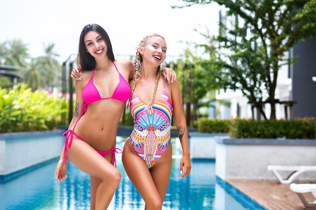 Яркий позитивный летний портрет хорошеньких девушек-подруг, позирующих у бассейна на тропических каникулах, в ярких купальниках, с идеальным стройным телом и длинными волосами. Бесплатные Фотографии