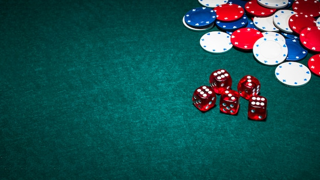 Bright red dices and casino chips on green poker background Free Photo