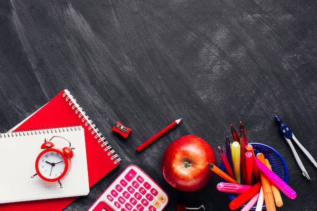 Bright red school supplies and apple on chalkboard Free Photo
