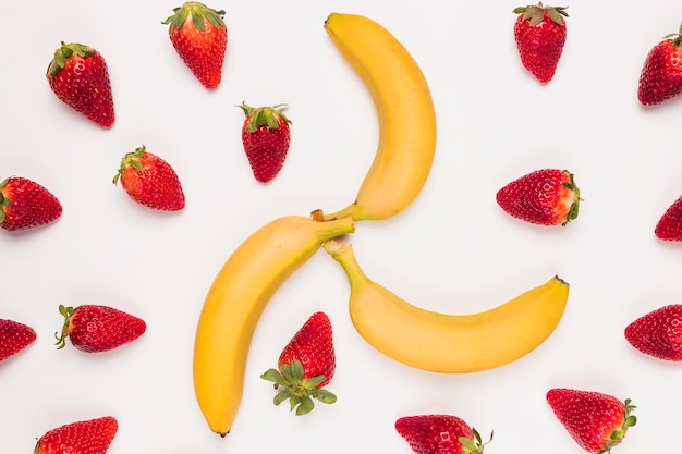 Bright red strawberry and yellow banana on white background Free Photo