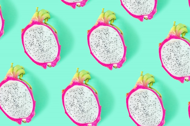 Bright rich background made of sliced dragon fruit or pitahaya on green. Premium Photo