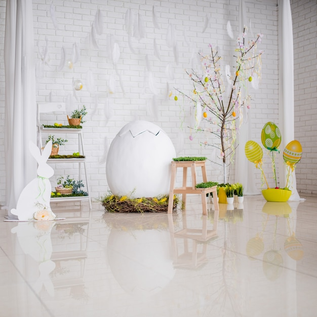 Bright studio prepared for easter and decorated with eggs and greenery Free Photo