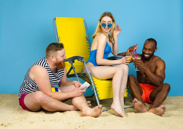 Светлое время. счастливые друзья отдыхают, пьют коктейли на синем фоне студии. концепция человеческих эмоций, выражения лица, летних каникул или выходных. холод, лето, море, океан, алкоголь. Бесплатные Фотографии