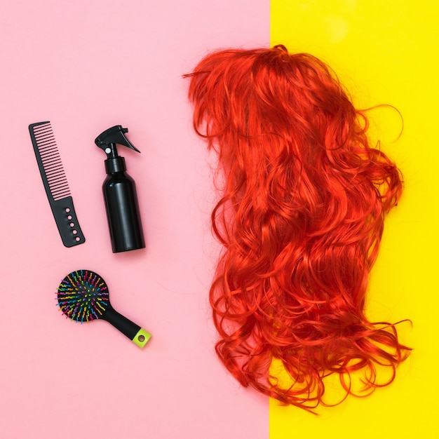 Bright wig, scissors and comb on a pink and yellow background. lifestyle. accessories to create style. Premium Photo