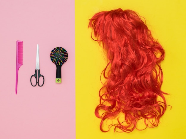 Bright wig, scissors and comb on a two-tone background. lifestyle. accessories to create style. Premium Photo