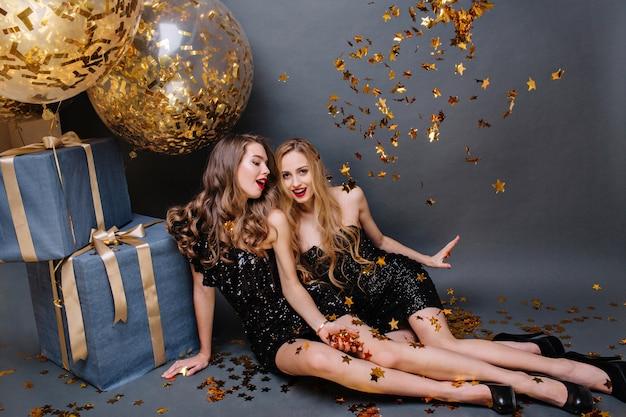 床で身も凍るような豪華な黒のドレスを着た2人の素晴らしい若い女性のパーティーを祝う明るい幸せな瞬間。お祝い、楽しんで、プレゼント、金色の見掛け倒し、笑顔。 無料写真