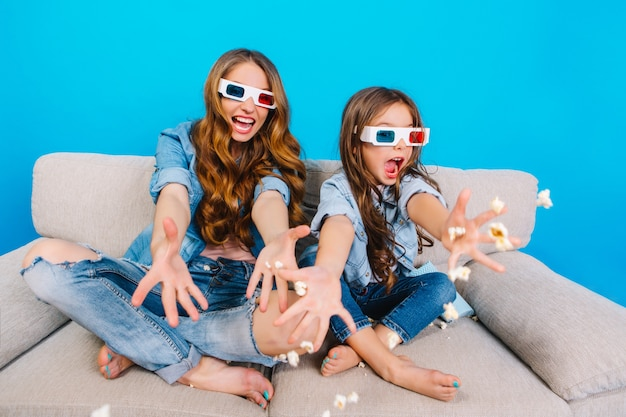 Яркие моменты довольно молодой матери, весело с дочерью на диване, изолированные на синем фоне. модный образ в джинсовой одежде, бросающий попкорн на камеру, безумный позитив Бесплатные Фотографии