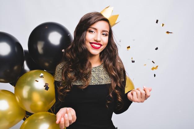 エレガントなファッションの黒のドレスと新年を祝う黄色い王冠のうれしそうな若い女性の明るいパーティー 無料写真