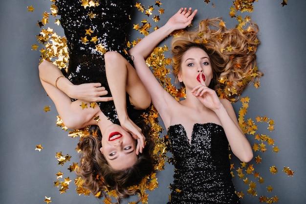 金色の見掛け倒しに横たわっている黒い高級ドレスを着た2人の楽しい魅力的な若い女性の上からの明るい肖像画。楽しんで、誕生日パーティー。 無料写真