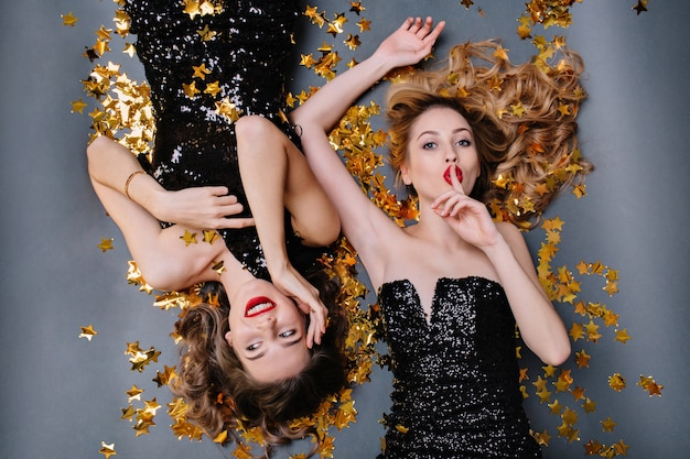 Brightful portrait from above two joyful attractive young women in black luxury dresses laying in golden tinsels. having fun, birthday party. Free Photo