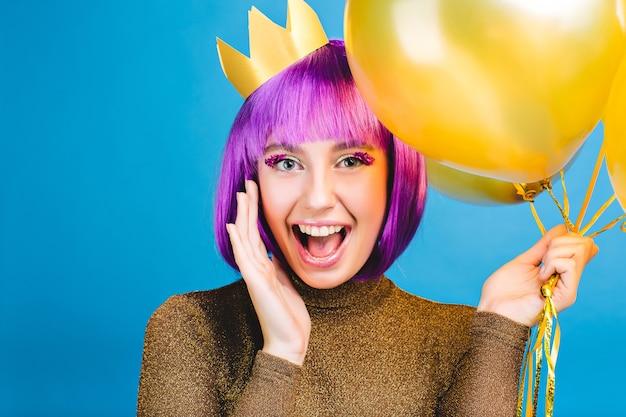 Brillanti emozioni positive a celebrare il nuovo anno, festa di compleanno di giovane donna gioiosa divertente con capelli viola tagliati. palloncini dorati, corona in testa, abito di lusso, felicità. Foto Gratuite