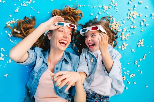 Яркое стильное изображение сверху взволновало мать и дочь, лежащих на синем полу в попкорне, смеясь в 3d-очках. счастливое семейное время, развлечение красивой мамы с ребенком, выражение счастья Бесплатные Фотографии
