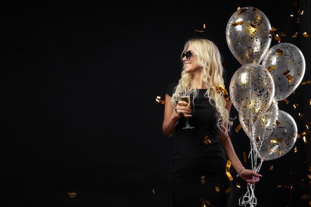 パーティーを祝う素晴らしいブロンドの女の子の幸せな感情のbrightfull表現。豪華な黒のドレス、笑顔、シャンパングラス、金色のティンセル、風船、長い巻き毛 Premium写真