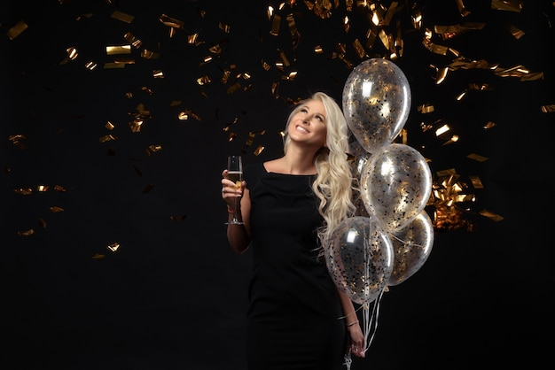 파티를 축하하는 놀라운 금발 소녀의 행복한 감정의 Brightfull 표현. 고급스러운 검은 드레스, 미소, 샴페인 한 잔, 황금색 반짝이, 풍선, 긴 곱슬 머리 프리미엄 사진