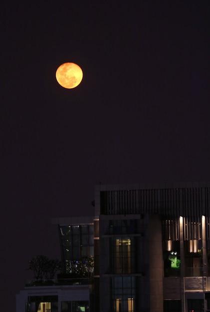 Brightly orange color full moon over the city of bangkok, thailand Premium Photo