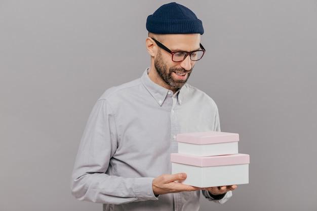 Brislteのハンサムな無精ひげを生やした男は、誕生日に友人からのプレゼントを喜んで受け取る2つのボックスを保持します Premium写真