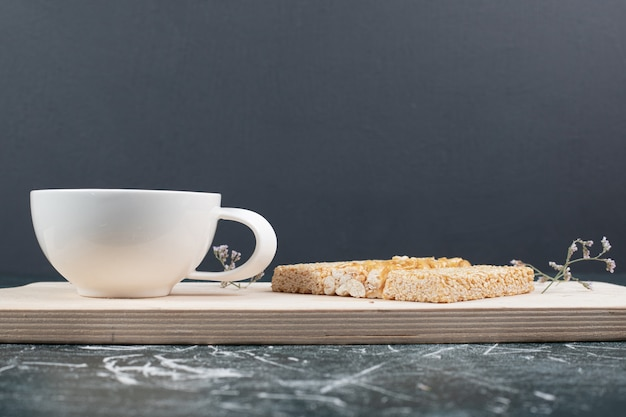 Brittle candies and cup of tea on wooden board. high quality photo Free Photo