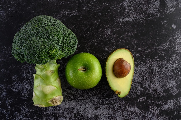 Broccoli, apple, and avocado on a black cement floor. Free Photo