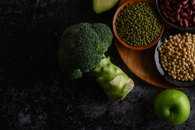 Broccoli, apple, and legumes on a black cement floor. Free Photo