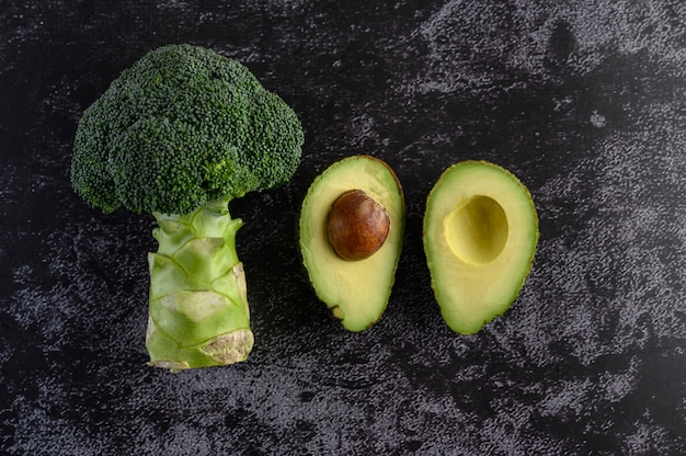 Broccoli and avocado on a black cement floor. Free Photo