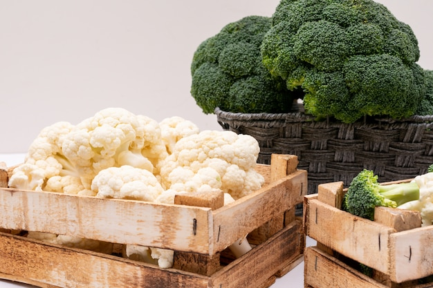 Broccoli and cauliflower in wooden box and broccoli in basket Free Photo
