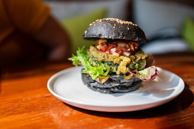 Broccoli quinoa charcoal burger topped with guacamole, mango salsa and fresh salad served on a white plate. creative vegan meal for vegetarians. Premium Photo