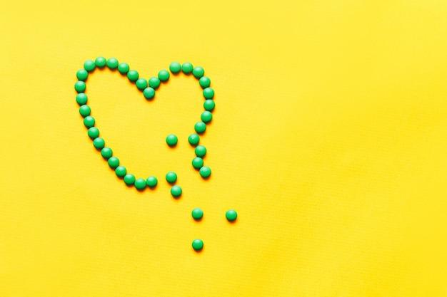 Зеленые круглые таблетки таблетки brocken форме сердца на желтом фоне Premium Фотографии