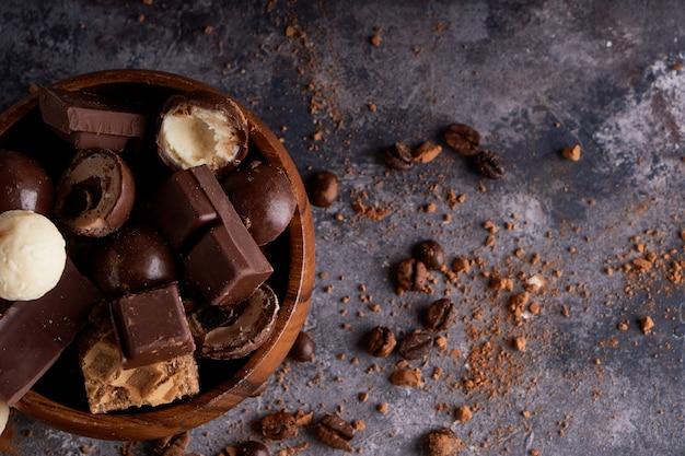 木製ボウルで壊れた黒と白のチョコレート。灰色の石のテーブルにチョコレートのかけら Premium写真