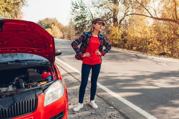 Broken car. sad woman standing on road by her auto with hood open stopping autos and waiting for help Premium Photo
