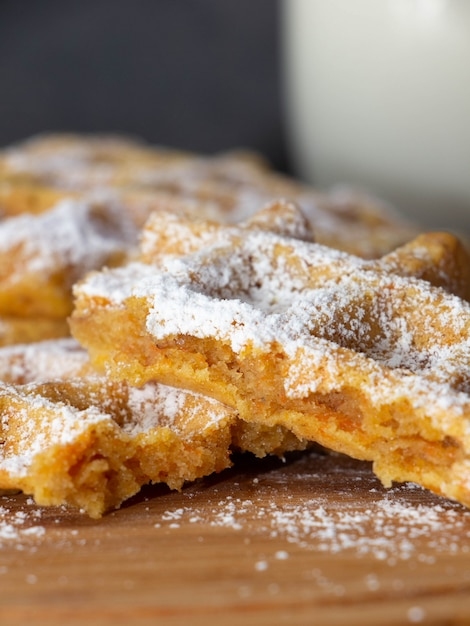 Broken carrot waffle dusted with icing sugar on a wooden board Premium Photo